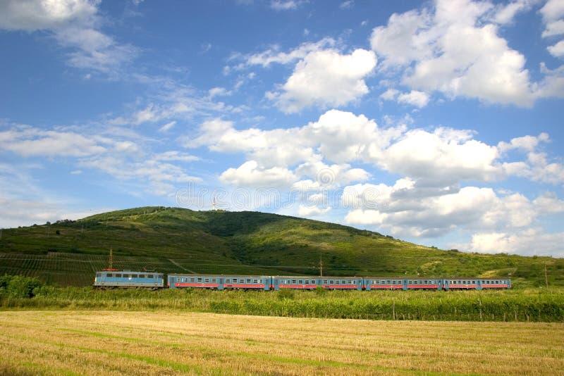 Passenger train at Tokaj. A passenger train under the Tokaj-hill, where the famous Hungarian Tokaji wine is producted. The train is hauled by a type V43 electric royalty free stock photo