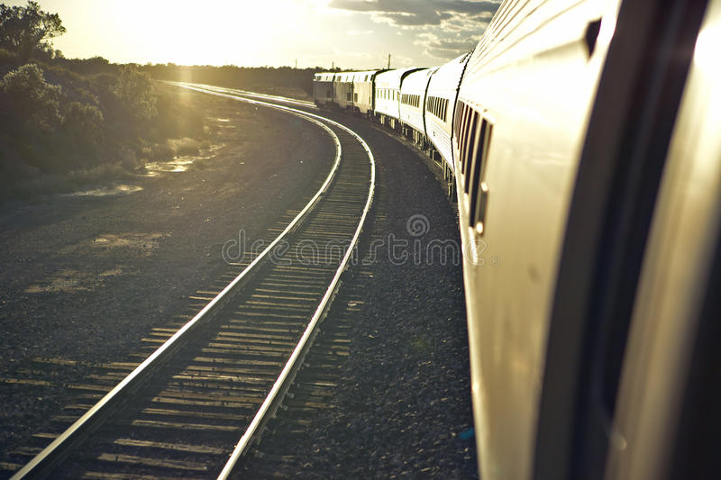 Passenger train traveling into the Arizona sunset stock image