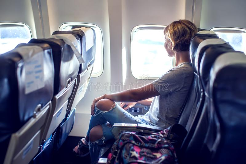 Passenger traveler looking at window in airplane, travel by flight, woman tourist sitting in air plane royalty free stock images