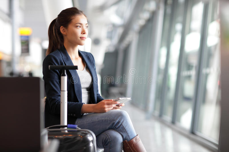 Passenger traveler woman in airport. Waiting for air travel using tablet smart phone. Young business woman smiling sitting with travel suitcase trolley, in royalty free stock photography