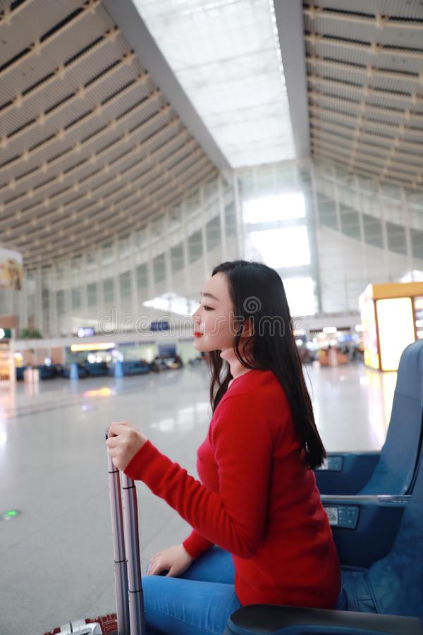 Passenger traveler woman in Train station. Waiting for air travel using tablet smart phone. Young business woman smiling sitting with travel suitcase trolley, in stock photos