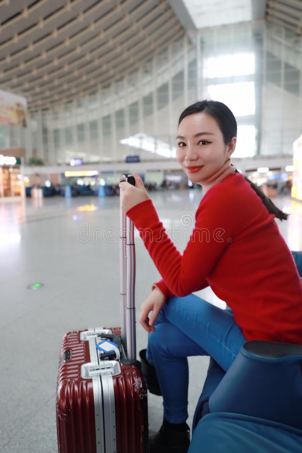 Passenger traveler woman in Train station. Waiting for air travel using tablet smart phone. Young business woman smiling sitting with travel suitcase trolley, in royalty free stock photography
