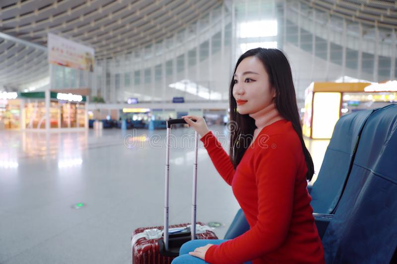 Passenger traveler woman in Train station. Waiting for air travel using tablet smart phone. Young business woman smiling sitting with travel suitcase trolley, in stock photography