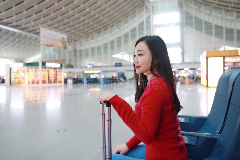 Passenger traveler woman in Train station. Waiting for air travel using tablet smart phone. Young business woman smiling sitting with travel suitcase trolley, in stock image