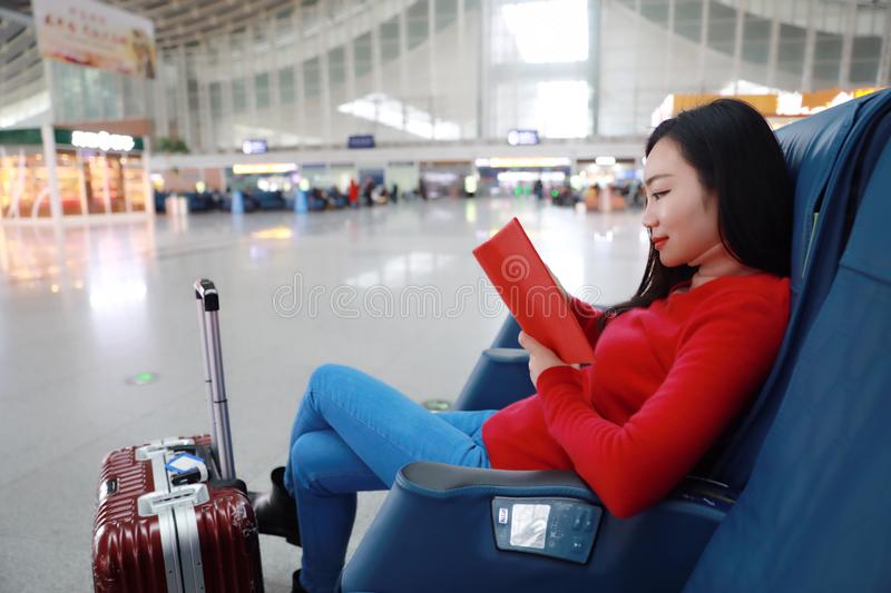 Passenger traveler woman in Train station and read book. Passenger traveler woman in Train stationwaiting for air travel using tablet smart phone. Young business royalty free stock images