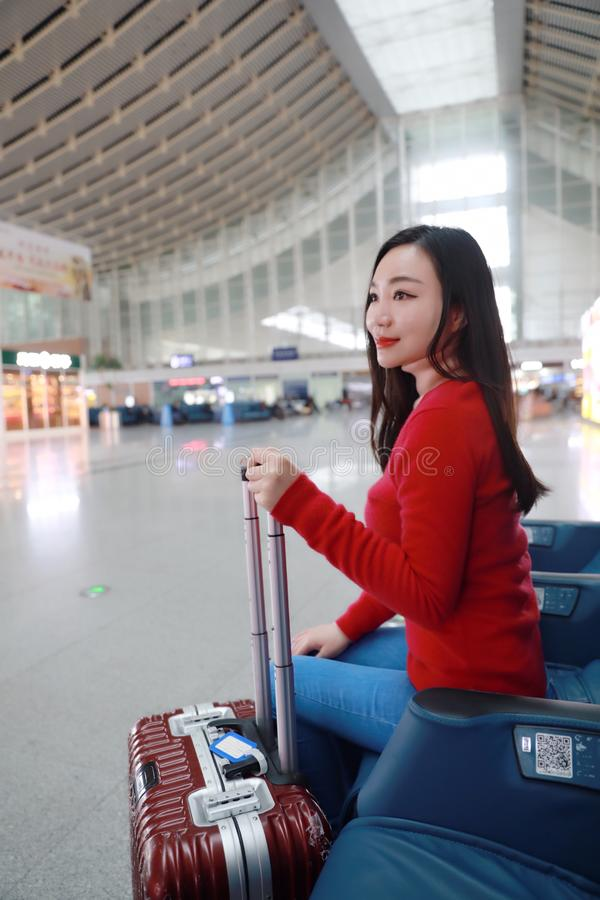 Passenger traveler woman in Train station. Waiting for air travel using tablet smart phone. Young business woman smiling sitting with travel suitcase trolley, in stock images