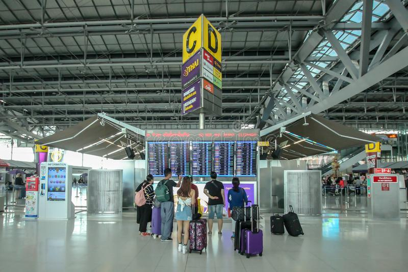 Passenger watching time schedule table of plane flight at Suvarnabhumi airport. royalty free stock photography