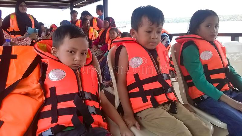 Passenger wear a safety jacket. MUAR, JOHOR - Disember 24, 2016 : Boat passengers ride on the boat and wear a safety jacket royalty free stock images