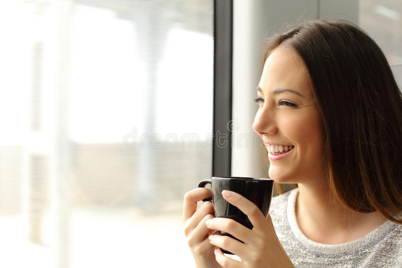 Passenger woman drinking coffee during a train travel. And looking through the window stock images