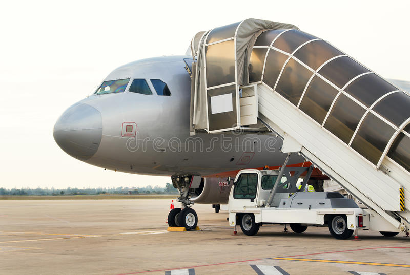 Passengers boarding jet on the tarmac in Cambodia. The shadowy shapes of boarding passengers show through the frosted panels of the gangway at the airport in royalty free stock image