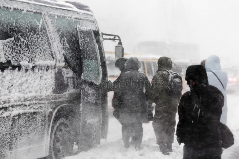 Passengers boarding on public transport - commercial city bus during blizzard snowfall stock photo