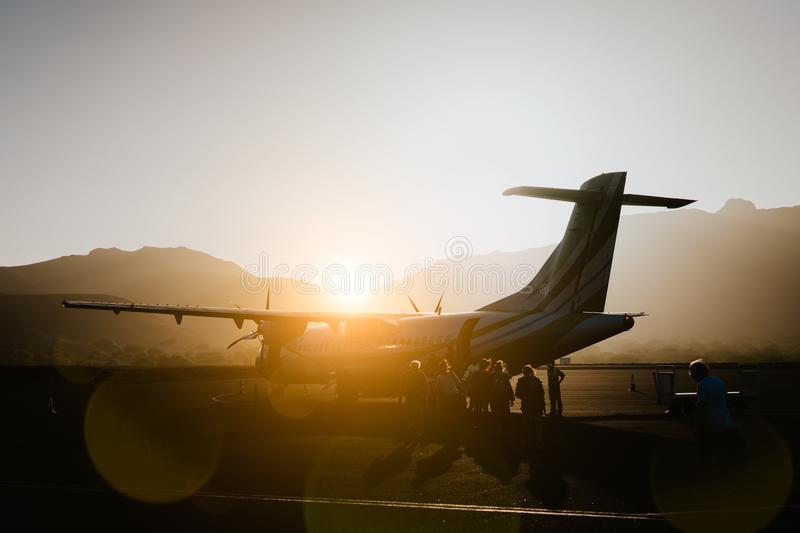 Passengers boarding to propeller aircraft on dusty morning. Mountain range surrounding runway on Sao Vicente airport royalty free stock image