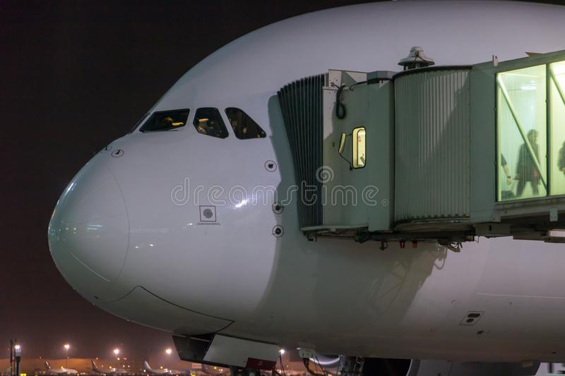 Passengers depart from the aircraft. The plane is standing by the tunnel at the night airport royalty free stock photos