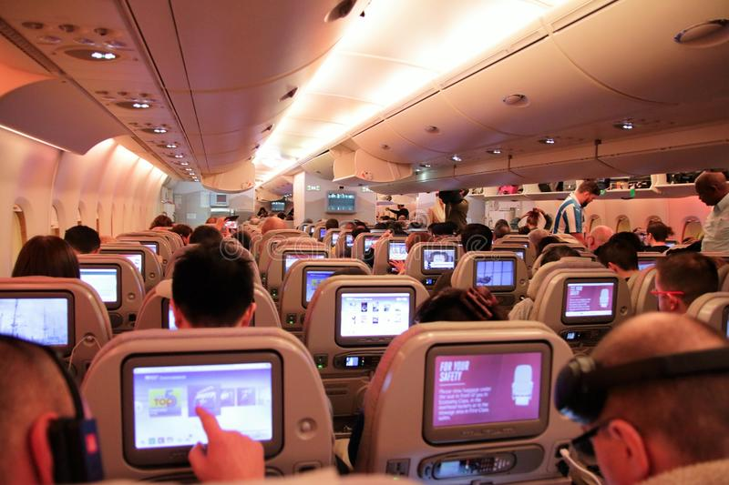 Passengers on an economy flight showing the seats and touch screens royalty free stock photo