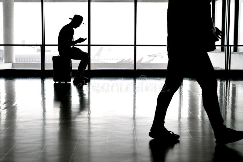 Passengers inside airport. Man in a hat with a cellphone sits on his travel bag in the airport hall on the large windows background. Another passenger walks past stock photos