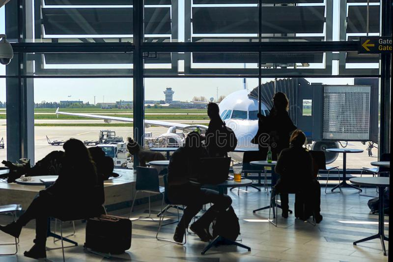 Passengers killing time in airport terminal, waiting to be boarded on to the plane stock photo