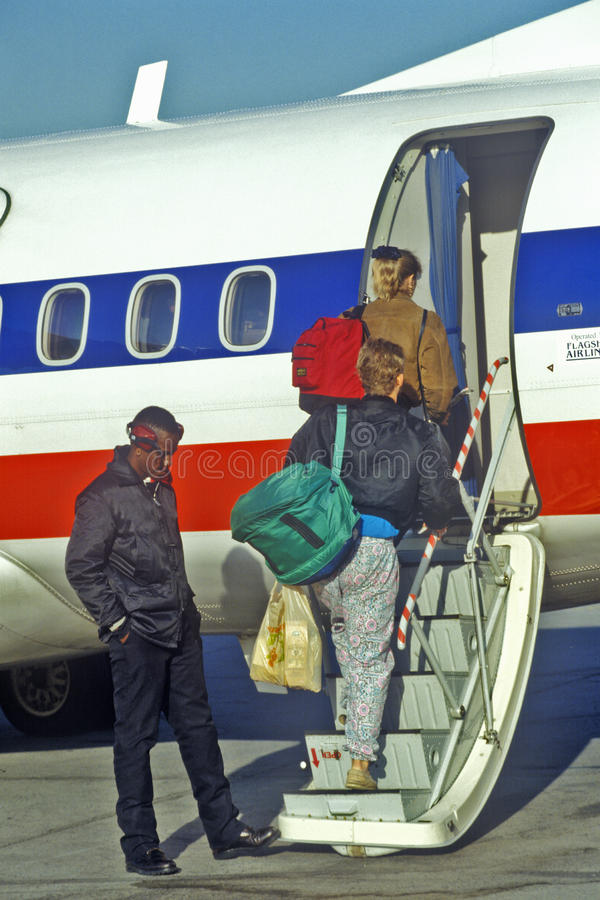 Passengers with luggage. And backpacks boarding small plane stock images