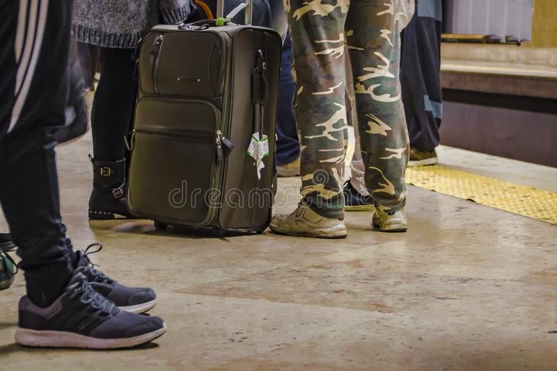 Passengers with luggage await transport at the stop.  stock photography