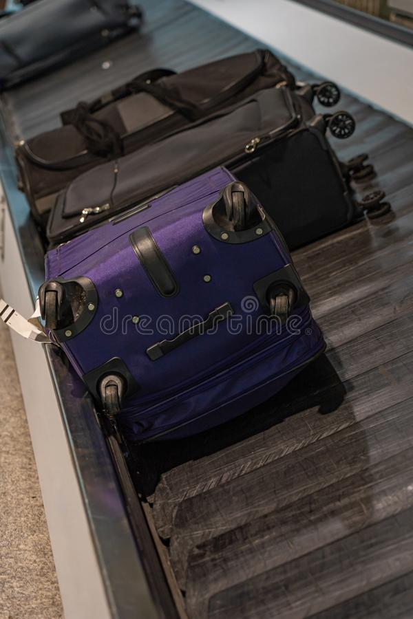 Passengers` luggage on the conveyor belt at airport arrival terminal. Passengers` luggage on the conveyor belt at airport arrival lounge royalty free stock image