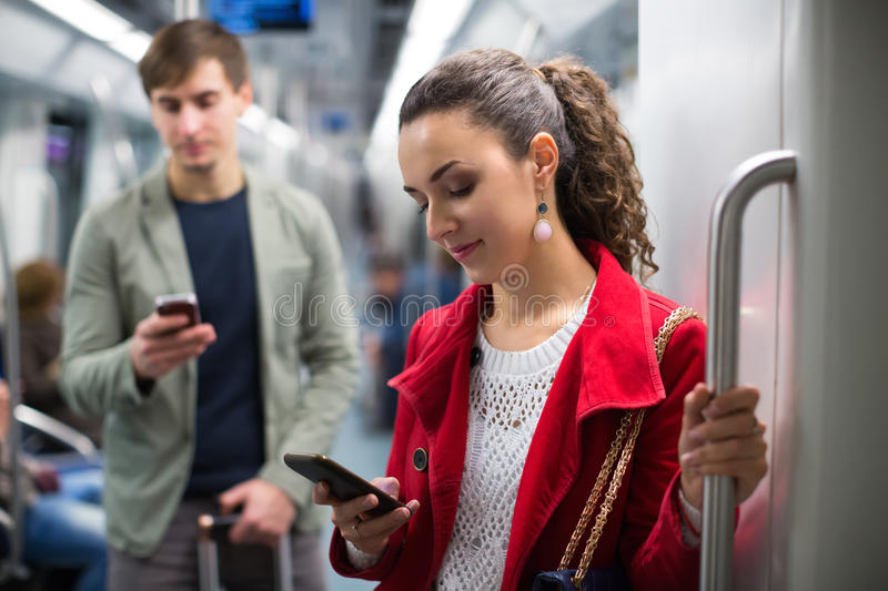 Passengers in metro wagon. Ordinary passengers reading news with mobile devices in metro wagon stock image