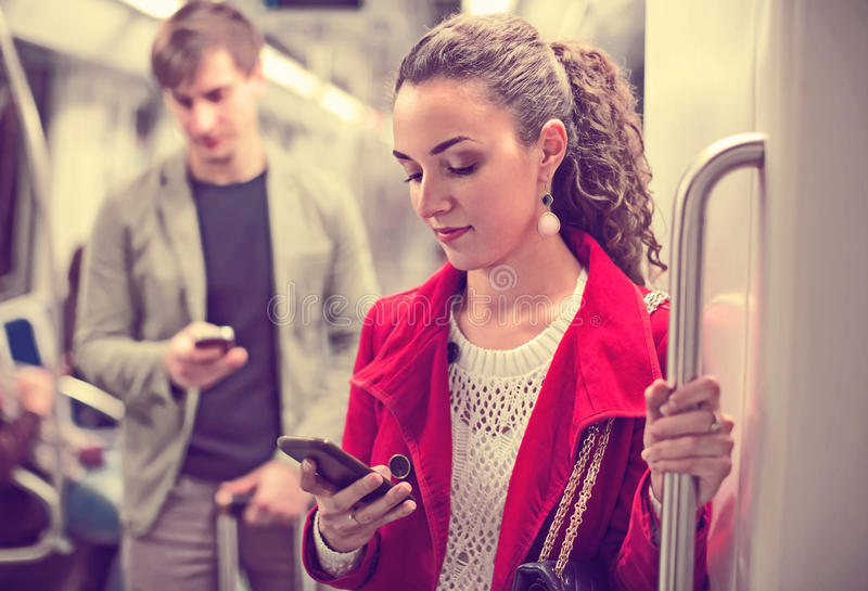 Passengers in metro wagon. Ordinary young passengers reading news with mobile devices in metro wagon stock image