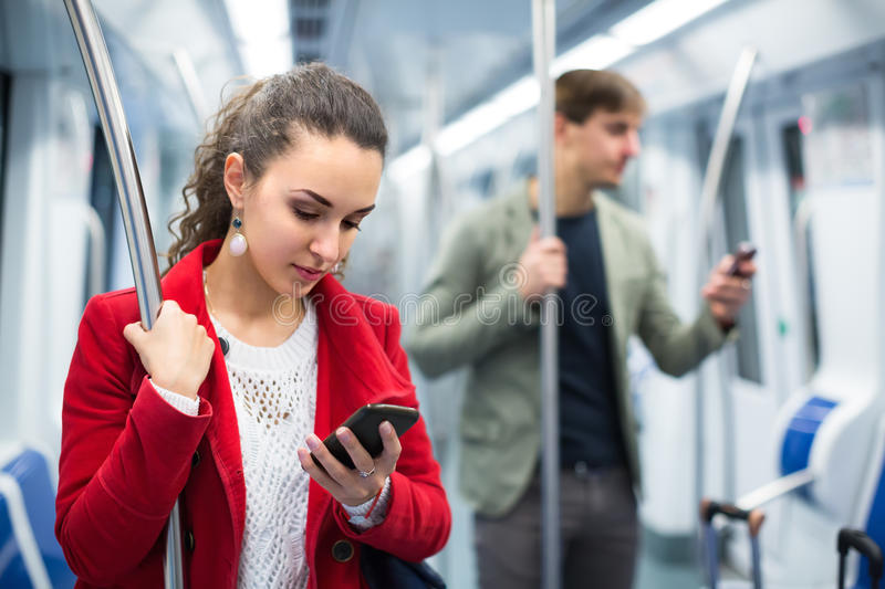 Passengers in metro wagon. Reading news with smartphones royalty free stock photography