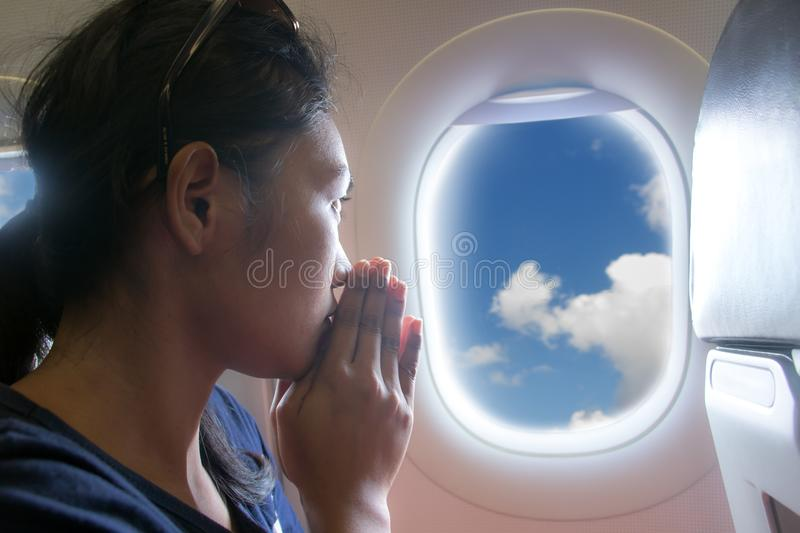 Passengers praying in a flying aircraft. While looking out of the window. Portrait of a woman looking out the window of a flying aircraft royalty free stock image