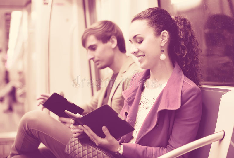 Passengers reading in metro wagon. Young passengers in metro wagon reading with electronic books stock image
