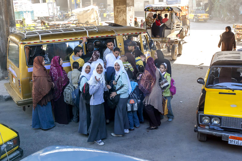 Passengers rush to board a small bus in Cairo, Egypt. Passengers rush to board a small mini bus parked under an overpass in Cairo, Egypt royalty free stock photo