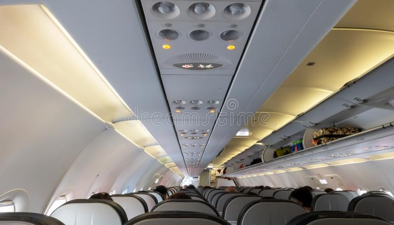 Passengers traveling by a plane. Travel concept. Roofs and seats inside the plane. stock images
