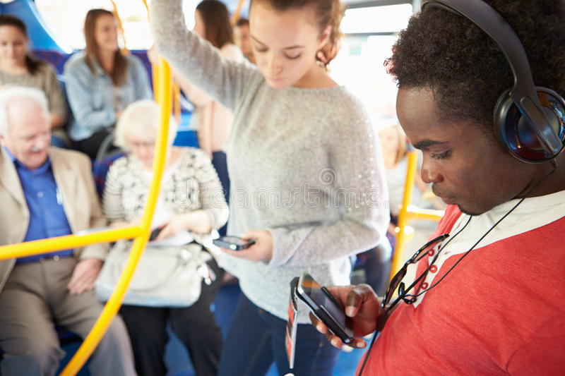 Passengers Using Mobile Devices On Bus Journey. Standing Up Holding Onto Poll royalty free stock images