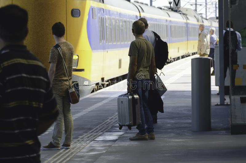 Passengers are waiting for the train that is approaching the platform at the station stock photos