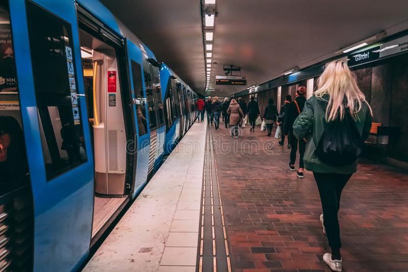 Passengers walking on the platform at Gärdet with a subway train waiting with the doors open stock image