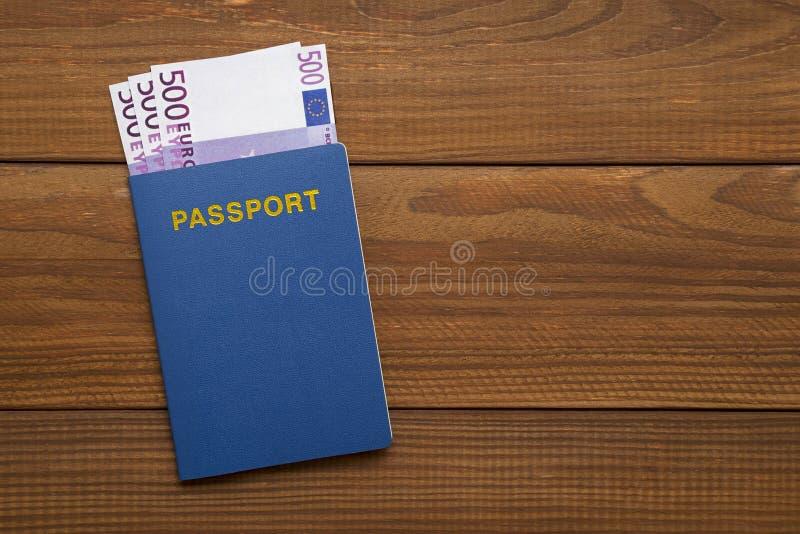 Passeport avec des euros sur la table en bois images stock