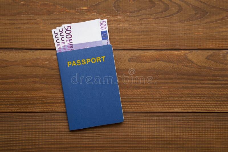 Passeport avec des euros sur la table en bois photographie stock