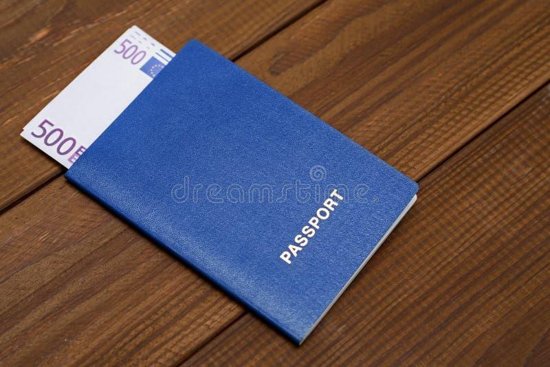 Passeport avec des euros sur la table en bois photographie stock libre de droits