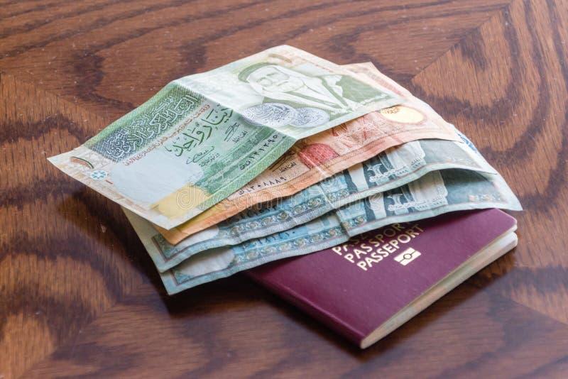 Passeport biométrique avec des billets de banque de dinar jordanien images stock