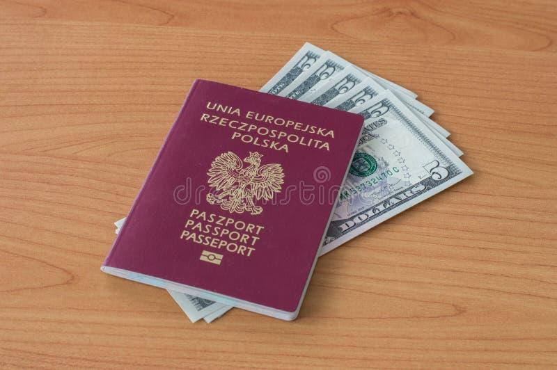 Passeport biométrique polonais avec cinq dollars de billets de banque photo stock