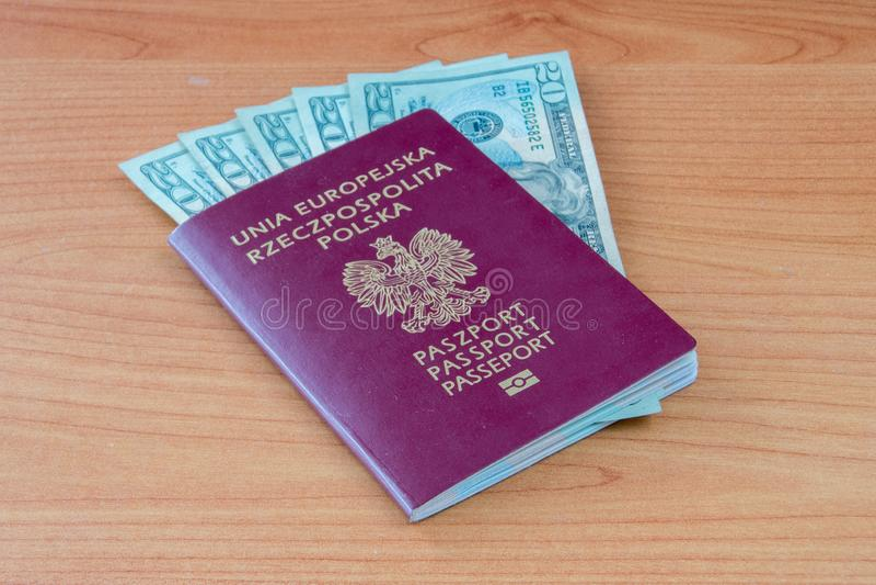 Passeport biométrique polonais avec vingt billets de banque du dollar d'Etats-Unis images stock