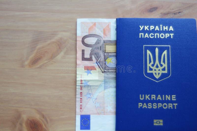 Passeport biométrique ukrainien avec le billet de banque de cinquante euros sur la table en bois photographie stock libre de droits