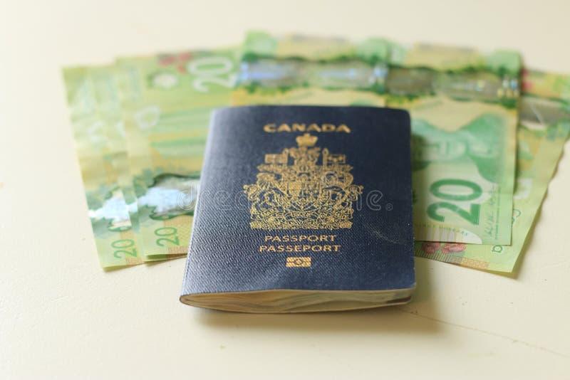 Passeport canadien s'étendant sur billets de vingt dollars Concept de l'immigration ou de l'émigration, ou du déplacement avec un photos stock