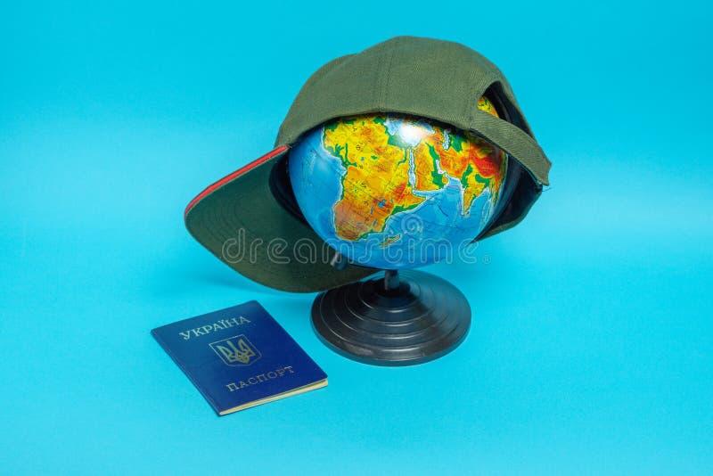 Passeport d'un citoyen de l'Ukraine pr?s du globe avec une casquette de baseball images stock