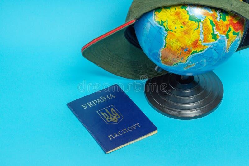 Passeport d'un citoyen de l'Ukraine pr?s du globe avec une casquette de baseball photos stock