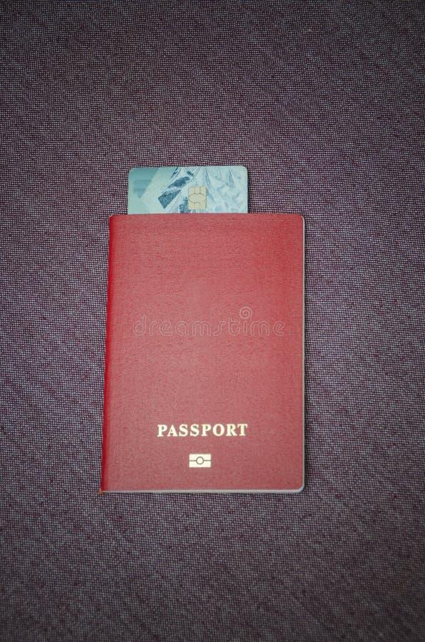 Passeport dans lequel la carte de crédit est attachée à la table photos stock