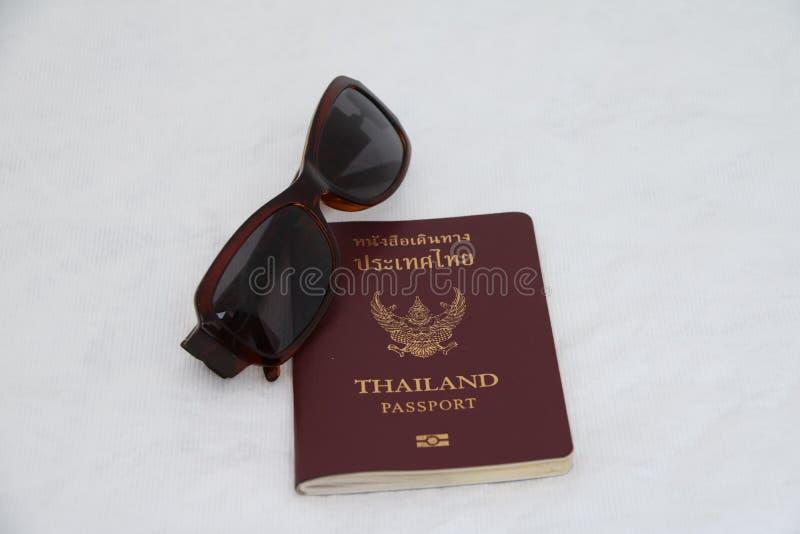 Passeport de la Thaïlande et isolat de lunettes de soleil sur le fond blanc Préparez pour voyager image stock