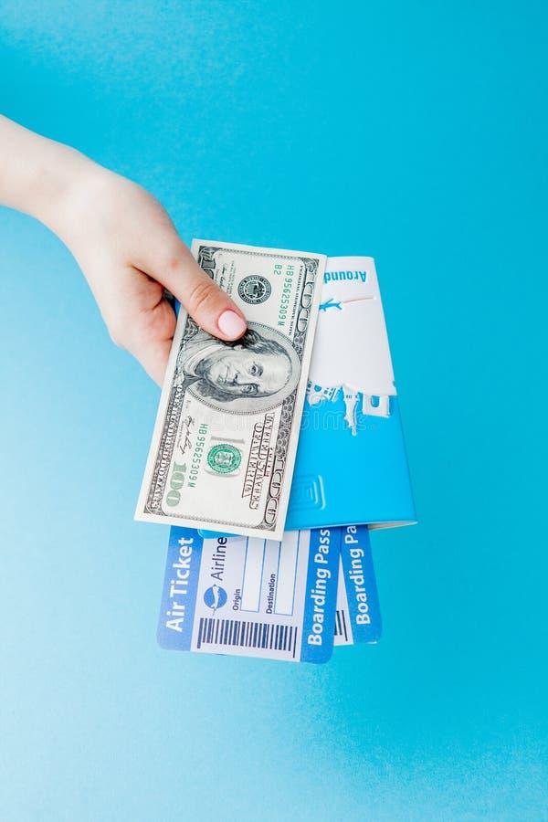 Passeport, dollars et billet d'avion chez la main de la femme sur un fond bleu r photo stock