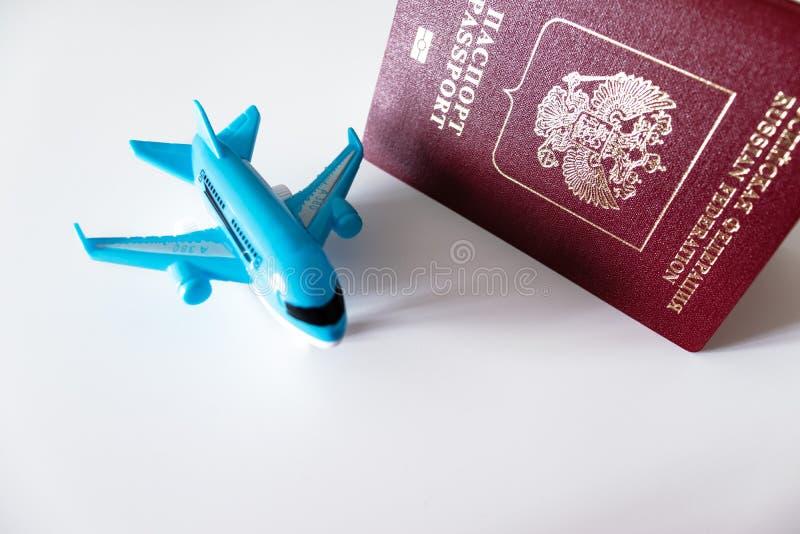 Passeport international russe et un avion bleu sur le fond blanc Voyage, voyage et concept volant photo stock