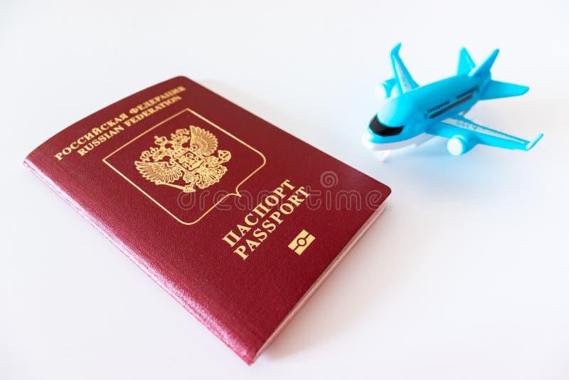 Passeport international russe et un avion bleu sur le fond blanc Voyage, voyage et concept volant images stock
