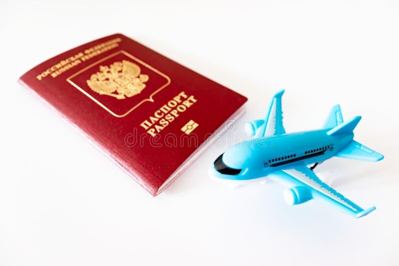 Passeport international russe et un avion bleu sur le fond blanc Voyage, voyage et concept volant photographie stock
