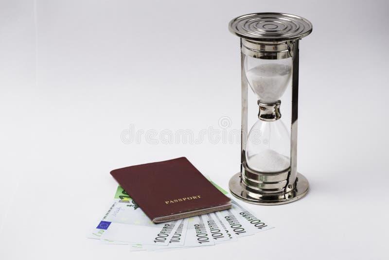 Passeport rouge avec d'euro billets de banque et sablier sur un fond blanc photo libre de droits